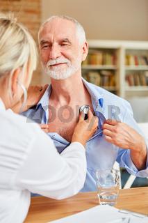 Ärztin untersucht Senior Mann mit dem Stethoskop