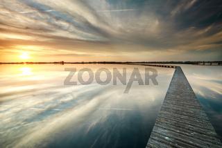 wooden walk way on big lake during sundown