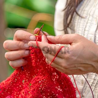 Hände einer Frau die mit roter Wolle häkelt / Strickt vor unscharfem Hintergrund