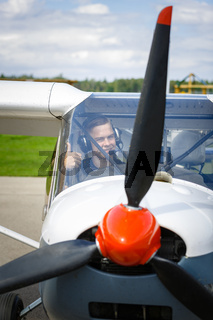 young man in small plane cockpit outdoors