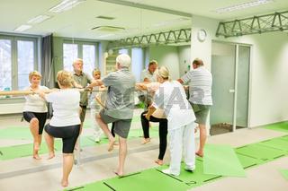 Therapeutin betreut Senioren bei Krankengymnastik