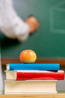 Closeup view, of a teacher desk with a pile of books and a red apple in front of a chalkboard.