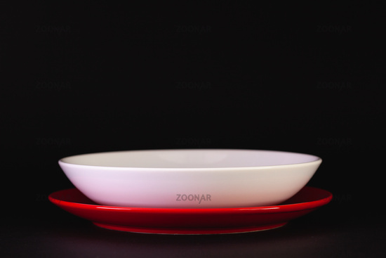 Red and white plates on the black table.