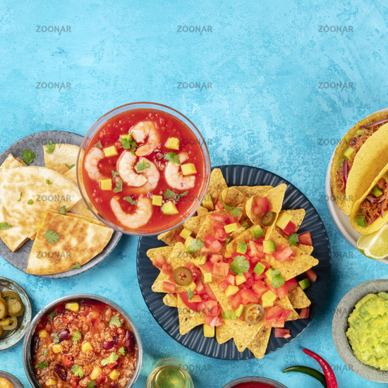 Mexican food, many dishes of the cuisine of Mexico, flat lay overhead square shot on a vibrant blue background with copy space. Shrimp cocktail, nachos, quesadillas, chili con carne