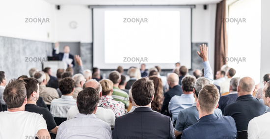 I have a question. Group of business people sitting in conference hall. Businessman raising his arm. Conference and Presentation. Business and Entrepreneurship