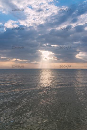 Sunbeams or sun rays peeking through the clouds at a sunrise at sea