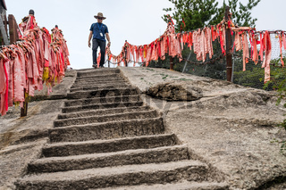 Tourist on the stone stairs to the summit of West Peak in Huashan mountain