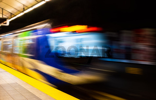 Colorful indoor abstract with motion blur of public transit subway train exiting station platform.