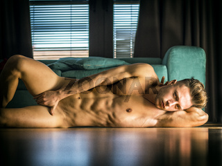 Totally naked muscular young man laying on floor