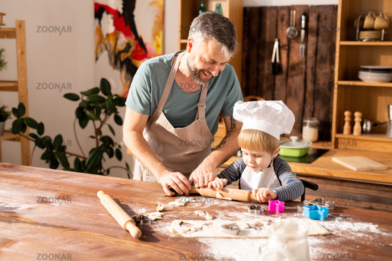 Cheerful father teaching son to roll dough