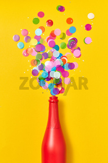 Colorful confetti as a bubble foam from painted red wine bottle.