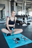 Frau trinkt Wasser zur Regeneration beim Training