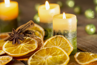 Christmas decoration - candles, spices and orange slices on wood