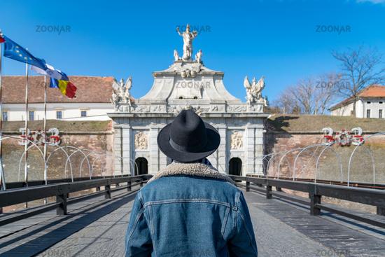 A tourist young man with a hat admiring a fortress gate entrance. A man admiring the 3rd Gate of the Alba-Carolina Fortress in Alba Iulia, Romania. Alba Iulia cityscape