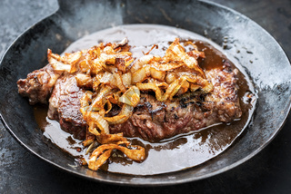 Traditional dry aged sliced roast beef with fried onion rings as closeup in a wrough-iron pan with brown sauce