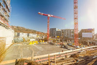 Large building site with foundations and cranes and scenic lens flare