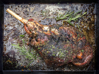Traditional barbecue leg of lamb with spice and herb as top view on a metal sheet