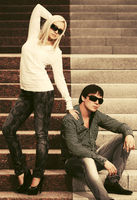 Happy young fashion couple in sunglasses on steps