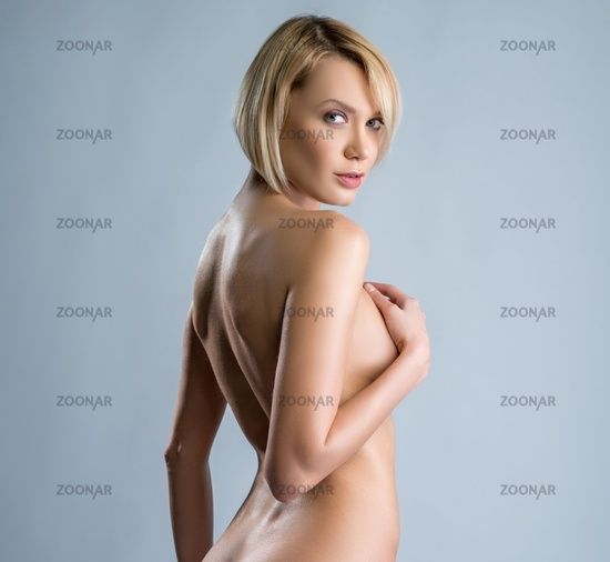 Naked woman looking over her shoulder coquettishly