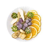Fruit slices orange, grapes, kiwi, pear and banana, on a plate isolated on white background. Top view.