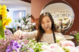 Asiatische Floristin in der Ausbildung im Blumenladen