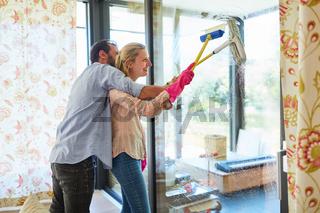 Fröhliches junges Paar beim Fenster putzen