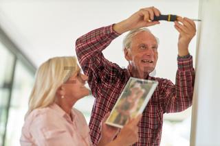 Senioren mit Schraubenzieher beim Foto aufhängen