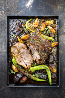 Barbecue marinated lamb roast with vegetable and potatoes as top view on a metal sheet
