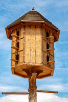 The wooden dovecote on the background of the blue sky