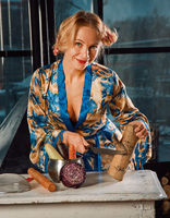 Blonde housewife cuts a wooden log into a pan