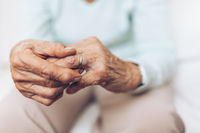 Heartbroken elderly woman holding he husbands wedding ring