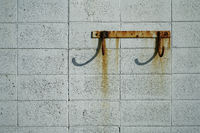 Rusty hooks on a breeze block wall.