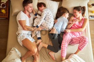 Kinder albern und spielen mit Eltern im Bett