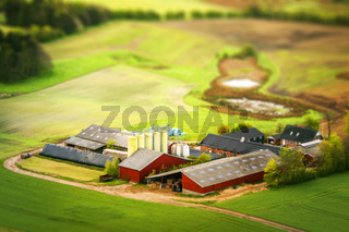 Rural farm in red colors with green fields