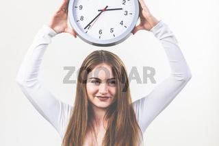 Frau, weißes Shirt und Jeans, brünette, lange Haare, hält eine Uhr in den Händen. Verabredung.