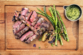 Barbecue dry aged wagyu porterhouse steak sliced with green asparagus
