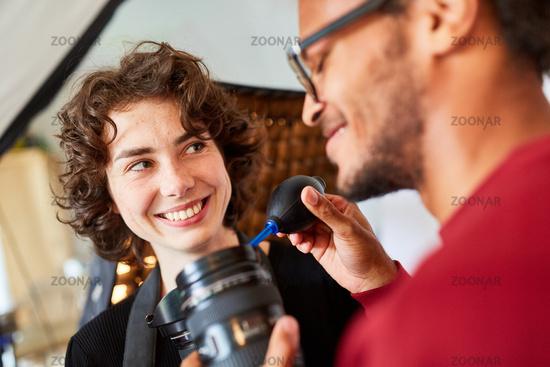 Fotograf bei Objektivreinigung mit Blasebalg