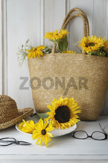 Closeup of sunflowers in straw purse on table