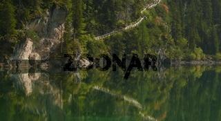 Bergsteig spiegelt sich im Wasser des Pragser Wildsees, Dolomiten,Suedtirol, Italien