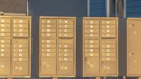 Panorama Row of mailboxes with numbers and compartments beside a road on a sunny day