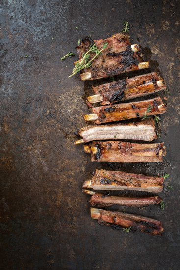 Barbecue spare ribs St Louis cut with hot honey chili marinade sliced as top view on an old rustic board