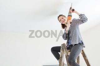 Heimwerkerin mit Bohrmaschine sitzt auf Leiter