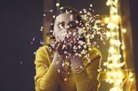 Happy beautiful brunette girl wearing yellow sweater blowing on confetti
