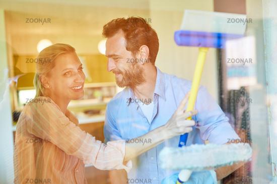 Mann als Hausmann hilft Frau beim Fenster putzen