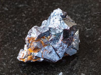 crystals of Cuprite stone on black granite