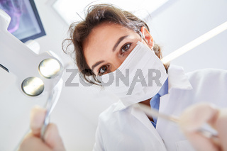 Junge Frau mit Mundschutz als Zahnärztin