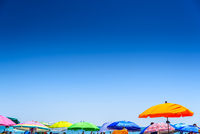 Colorful beach umbrella stuck in the sand surrounded by a group of bathers in summer, near the Mediterranean sea.