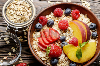 Flat lay of fruit healthy muesli with peaches strawberry almonds and blackberry in clay dish on wooden kitchen table