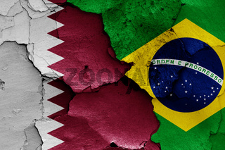 flags of Qatar and Brazil painted on cracked wall
