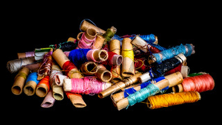 Pile of used colorful spools of thread tailoring, on black background